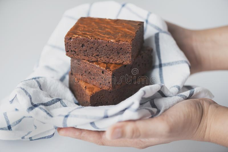 Woman hands holding a chocolate brownie mat with clothes on white background stock photo