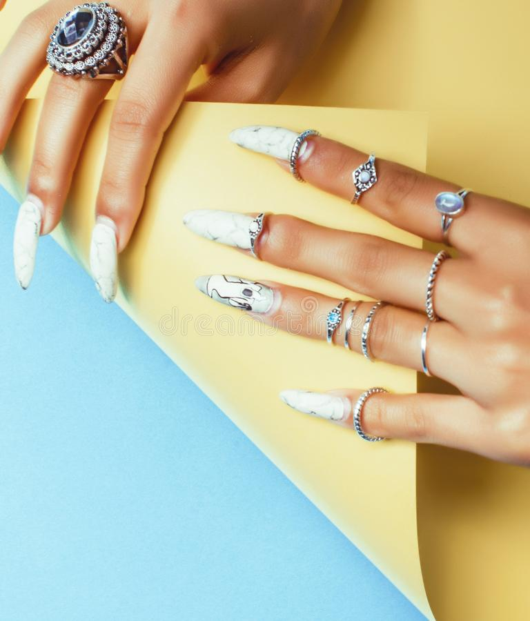 Woman hands holding colorful paper copyspace wearing a lot of jewelry and long nails. Closeup royalty free stock photo
