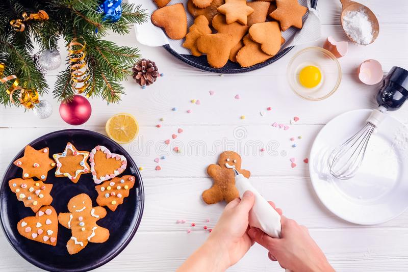 Woman hands holding a culinary bag with meringue cream inprocess of decorating gingerbread man cookies. White wooden table with in. Grediens and decoration stock images