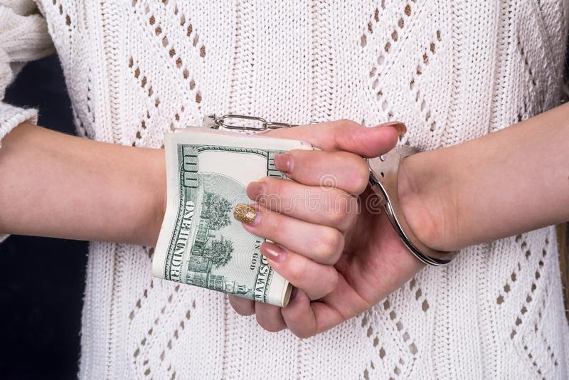 Woman hands holding dollar banknotes in handcuffs behind back. stock photography