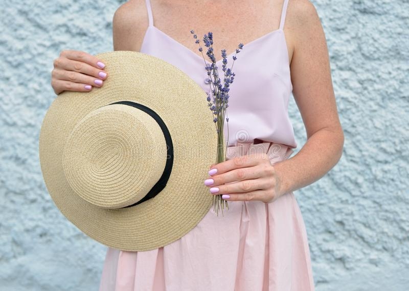 Woman hands holding dry natural lavender flowers bunch and straw hat with black ribbon royalty free stock photos