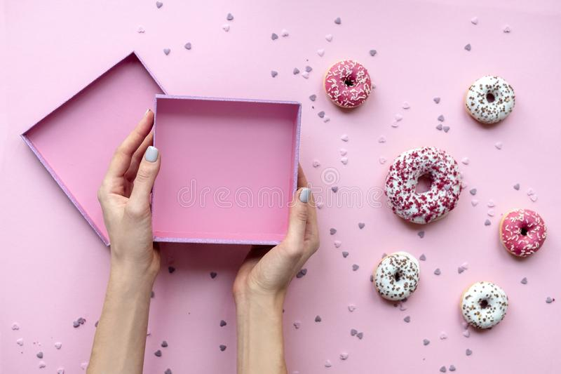 Woman hands holding empty box. Pink background with donuts. Woman hands holding empty box. Pink background with different donuts stock images