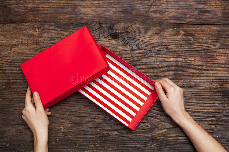 Woman hands holding empty gift box on wooden background. Woman hands holding empty gift box on the wooden background stock photo