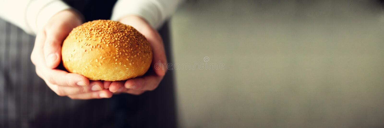 Woman hands holding freshly baked bread. Bun, cookie, bakery concept, homemade food, healthy eating. Copy space. Banner. Woman hands holding freshly baked bread stock photos