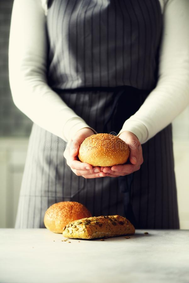 Woman hands holding freshly baked bread. Bun, cookie, bakery concept, homemade food, healthy eating. Copy space. Banner. Woman hands holding freshly baked bread royalty free stock image