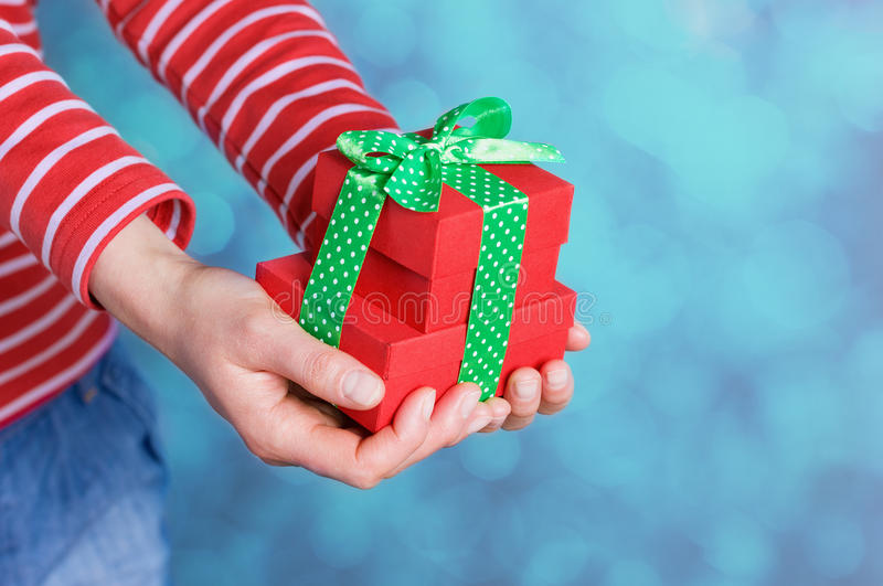 Woman hands holding a gift or present box with bow of green ribbon for Valentines Day. Photo with bokeh at background royalty free stock images
