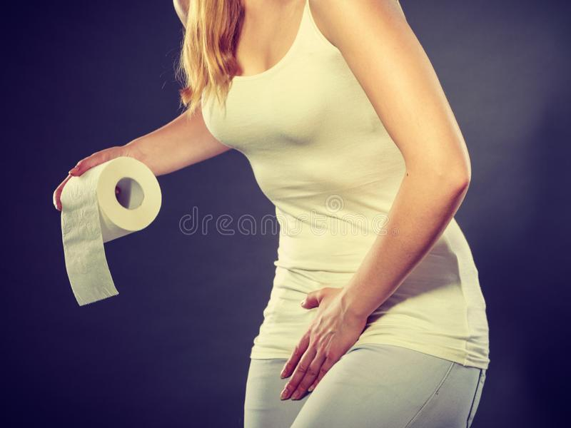 Woman with hands holding her crotch in toilet stock photos