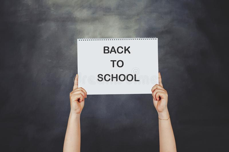 Woman hands holding high a post card that says BACK TO SCHOOL against a blackboard stock photo