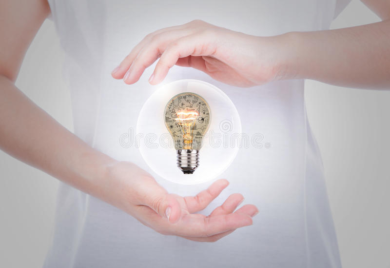 Woman hands holding light bulb with business concept inside. Over body stock images