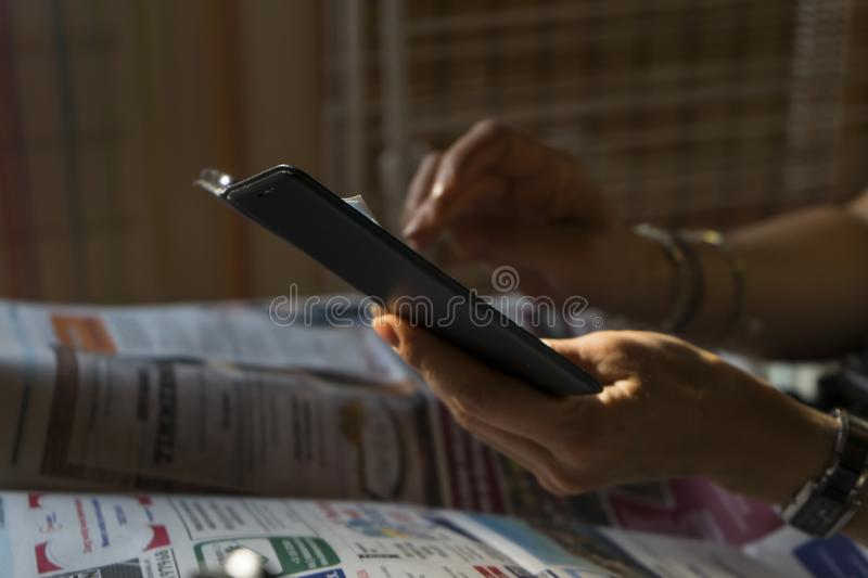Woman hands holding a mobile smartphone and is tapping on it. Black phone sharp close up with blurred background. Two female white stock images