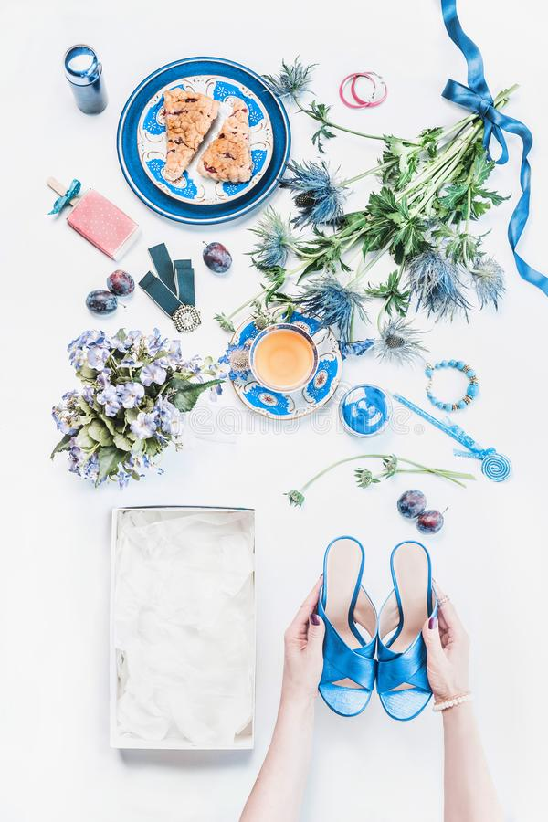 Woman hands holding new blue sandals on white desktop with empty box and feminine still life of cosmetic products, flowers bunch, royalty free stock photo