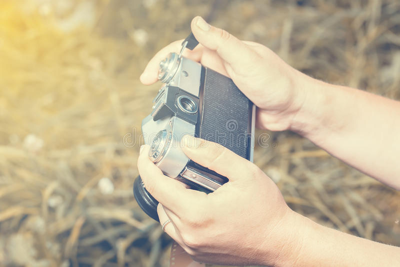 Woman hands are holding old vintage film camera outdoors. Toned. stock photo
