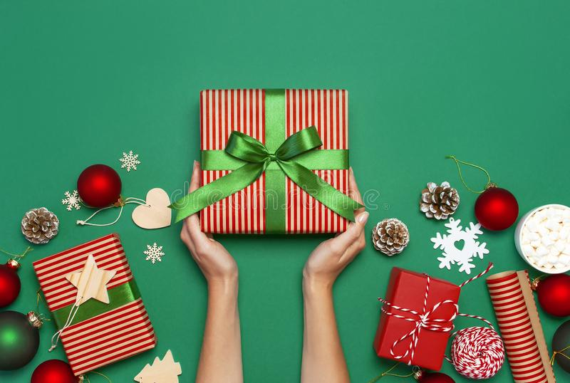 Woman hands holding present box, Christmas balls, toys, fir cones, ribbon on green background. Festive congratulation New Year Chr royalty free stock photos
