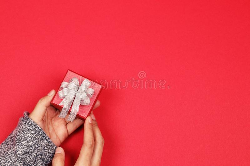 Woman hands holding red gift box with copy space. Flat lay. Top royalty free stock images