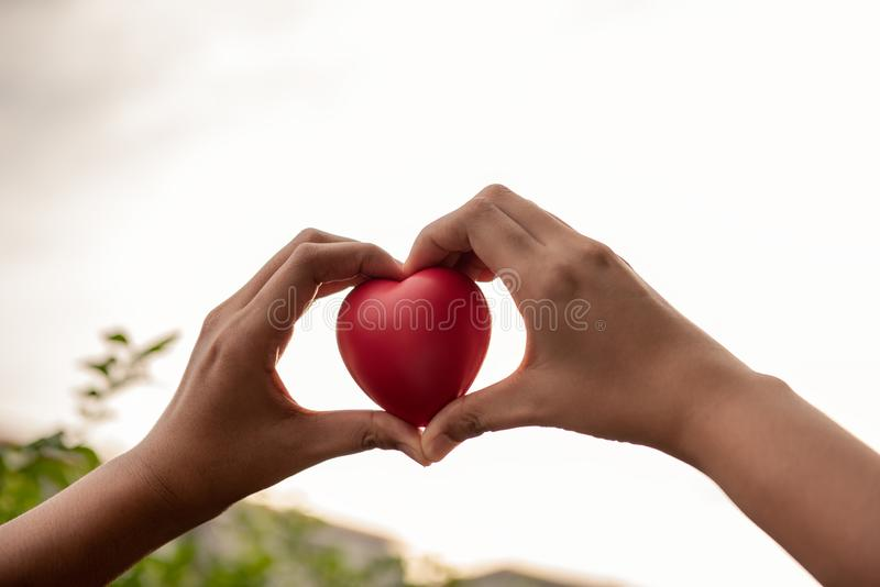 Woman hands is holding red heart to giving someone royalty free stock images