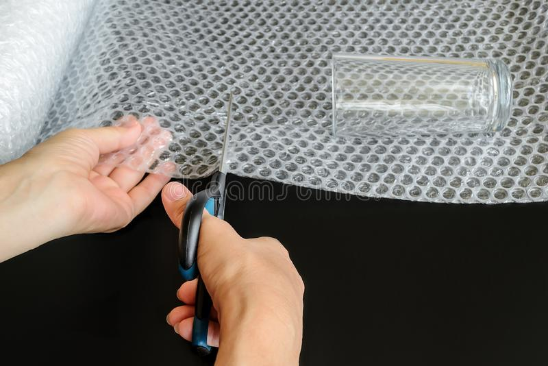 Woman hands holding a scissors and cutting a piece of white transparent bubble wrap for to wrap up a glass. On a black background royalty free stock images