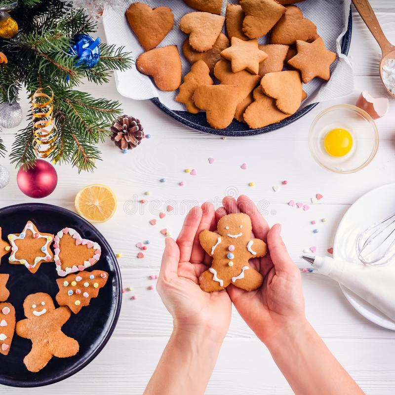 Woman hands holding traditional christmas gingerbread man cookies. White wooden table with ingrediens and decoration details. Chri. Stmas concept. The process of royalty free stock photos