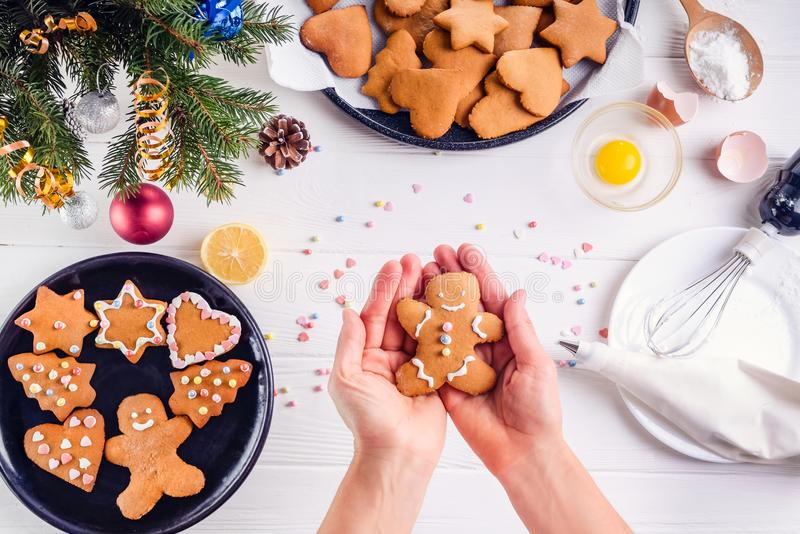 Woman hands holding traditional christmas gingerbread man cookies. White wooden table with ingrediens and decoration details. Chri. Stmas concept. The process of royalty free stock photo