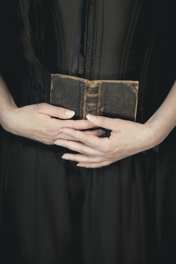 Woman hands holding vintage old book, very dark atmospheric sensual rural, gothic studio shot. Can be used as background stock photo