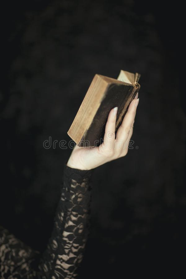 Woman hands holding vintage old book, very dark atmospheric sensual rural, gothic studio shot. Can be used as background royalty free stock image
