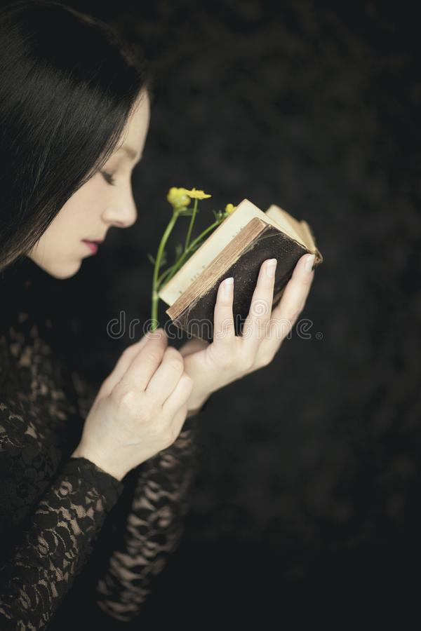 Woman hands holding vintage old book, very dark atmospheric sensual rural, gothic studio shot. Woman hands holding vintage old book with flower, very dark royalty free stock photography