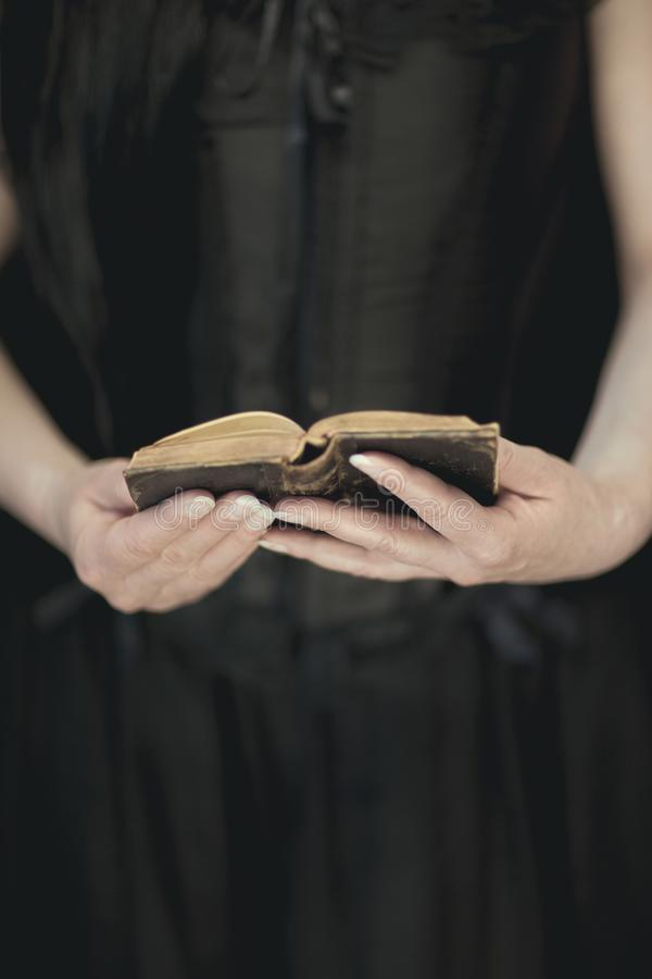 Woman hands holding vintage old book, very dark atmospheric sensual rural, gothic studio shot. Can be used as background stock photography