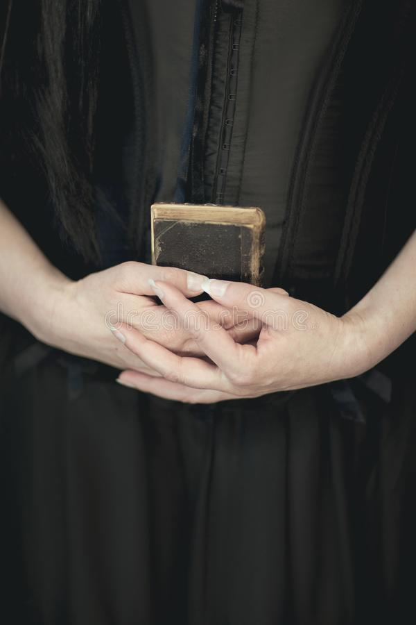 Woman hands holding vintage old book, very dark atmospheric sensual rural, gothic studio shot. Can be used as background stock image