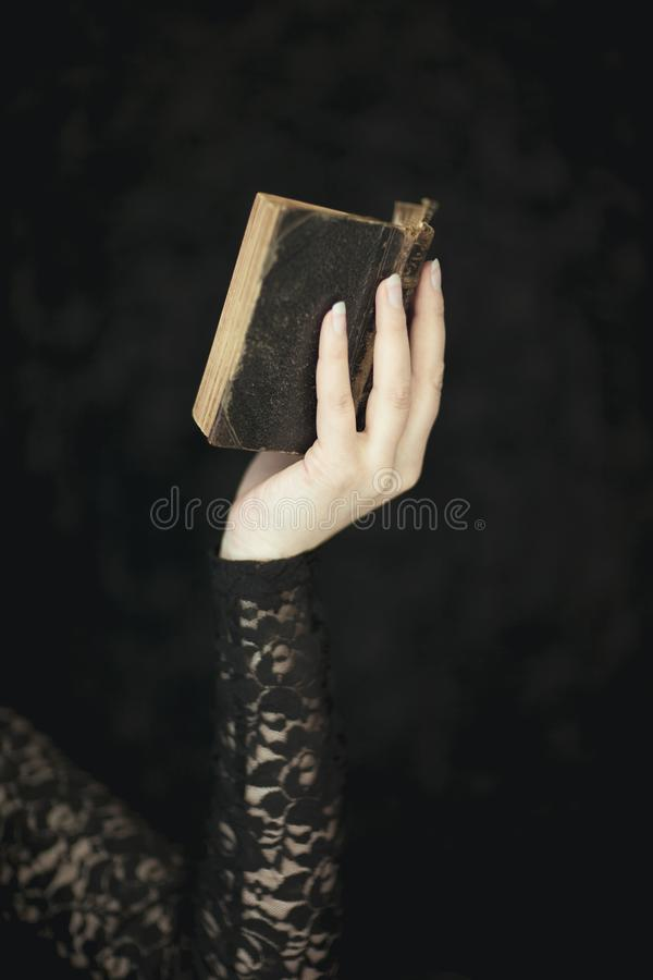 Woman hands holding vintage old book, very dark atmospheric sensual rural, gothic studio shot. Can be used as background stock photos