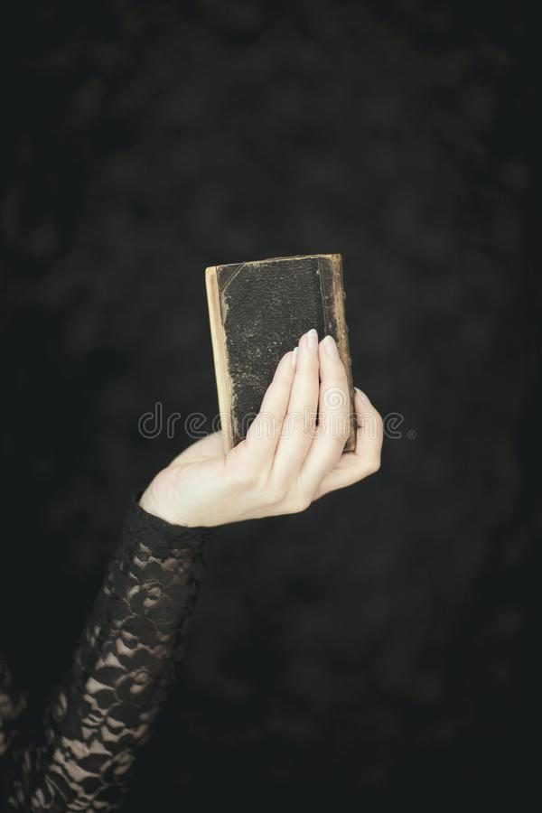 Woman hands holding vintage old book, very dark atmospheric sensual rural, gothic studio shot. Can be used as background royalty free stock images