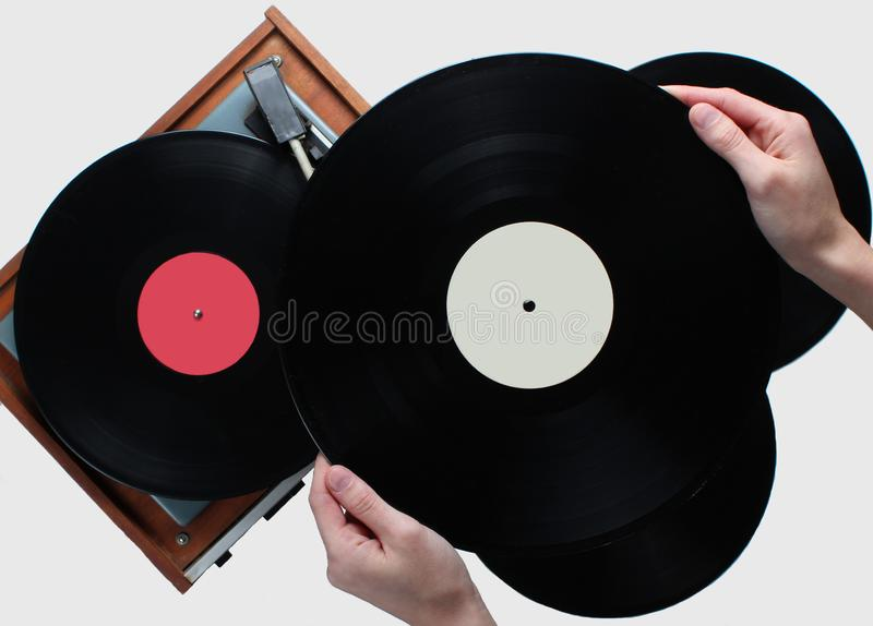 Woman hands holding vinyl record, vinyl player. With records on white background. Retro style, 80s, top view stock image