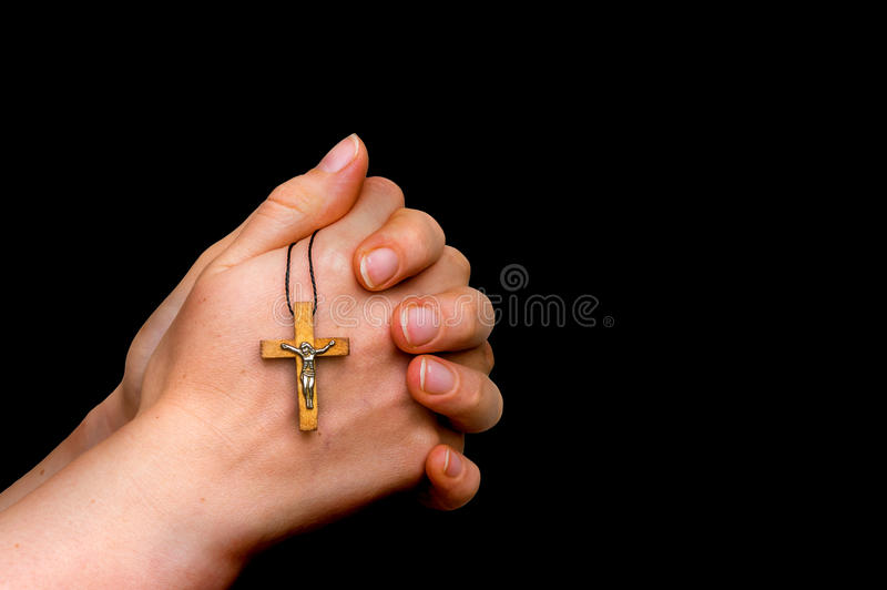 Woman hands holding wooden cross isolated on black stock photography