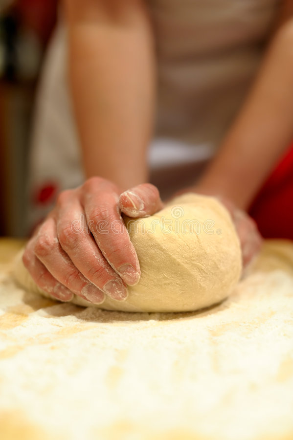 Woman hands kneading dough. On the table stock photography