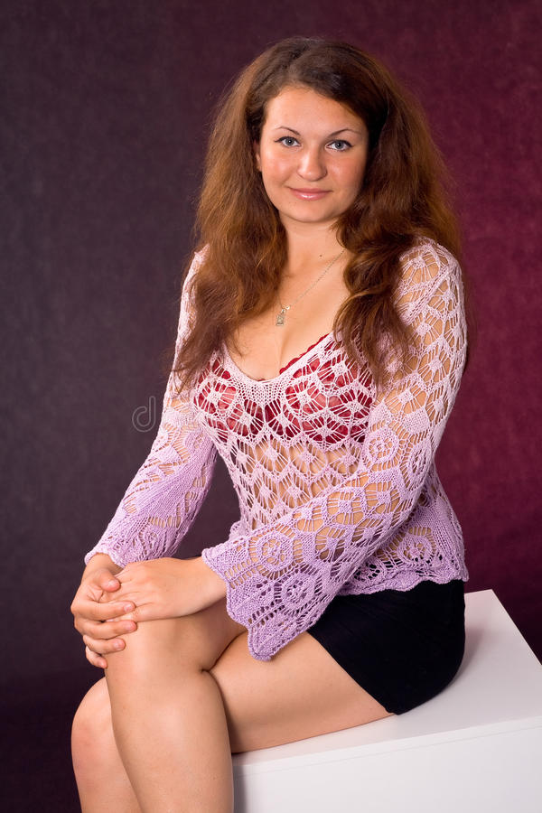 Woman with hands on knees. Charming woman sitting on the cube, with hands on knees stock photos