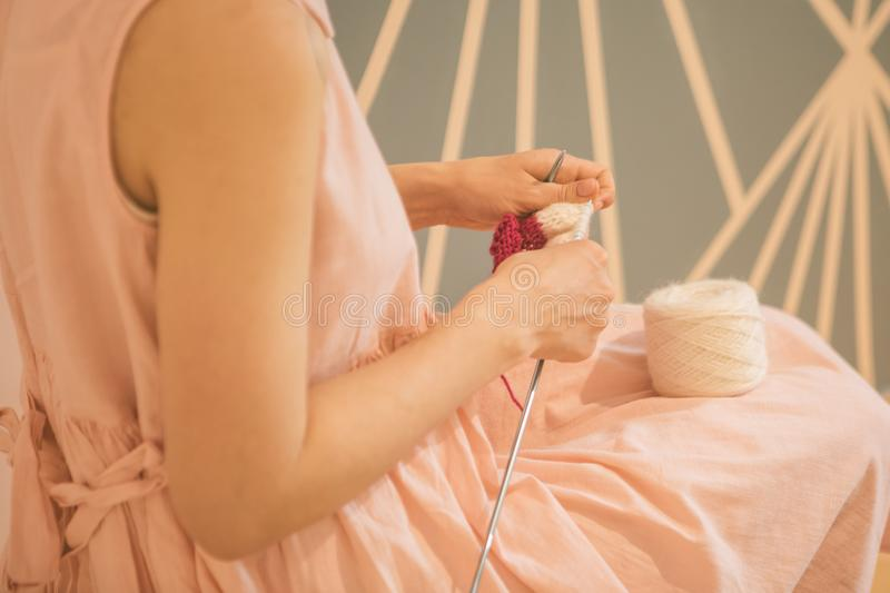 Woman hands knitting needles. hobby crafts things. Top view. Horizontal composition. Pink warm colors. New mainstream. Hipster hobby. Pink dress, relaxed mood stock images