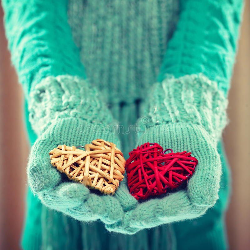 Woman hands in light teal knitted mittens are holding a beautiful red hearts. Love and St. Valentine concept. Instagram filter royalty free stock photo