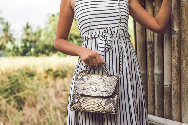 Woman hands with luxury handmade snakeskin leather handbag. Python snake fashionable handbag. Outdoors, Bali island. royalty free stock photo