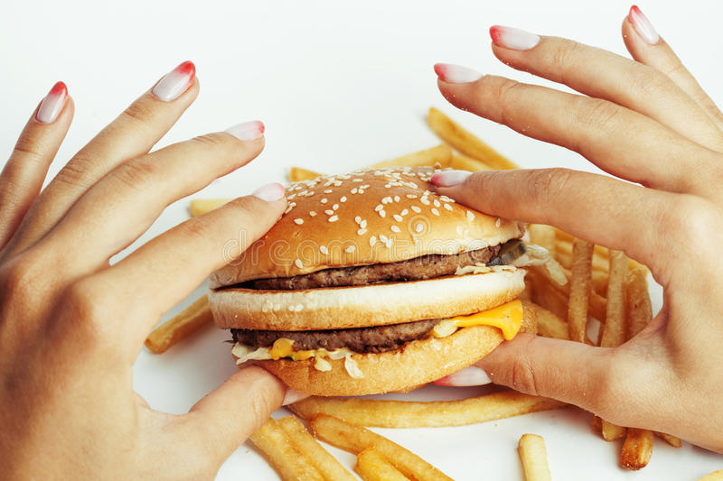 Woman hands with manicure holding hamburger and. French fries isolated on white royalty free stock image