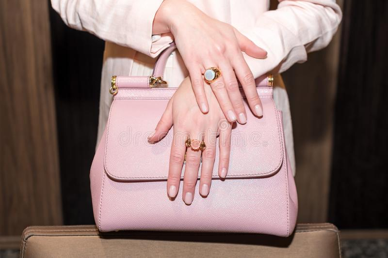 Woman hands with manicure and luxury jewelry rings. Close up of trendy leather pink bag with female hands showing. Fashion jewelry at camera. Concept of royalty free stock image