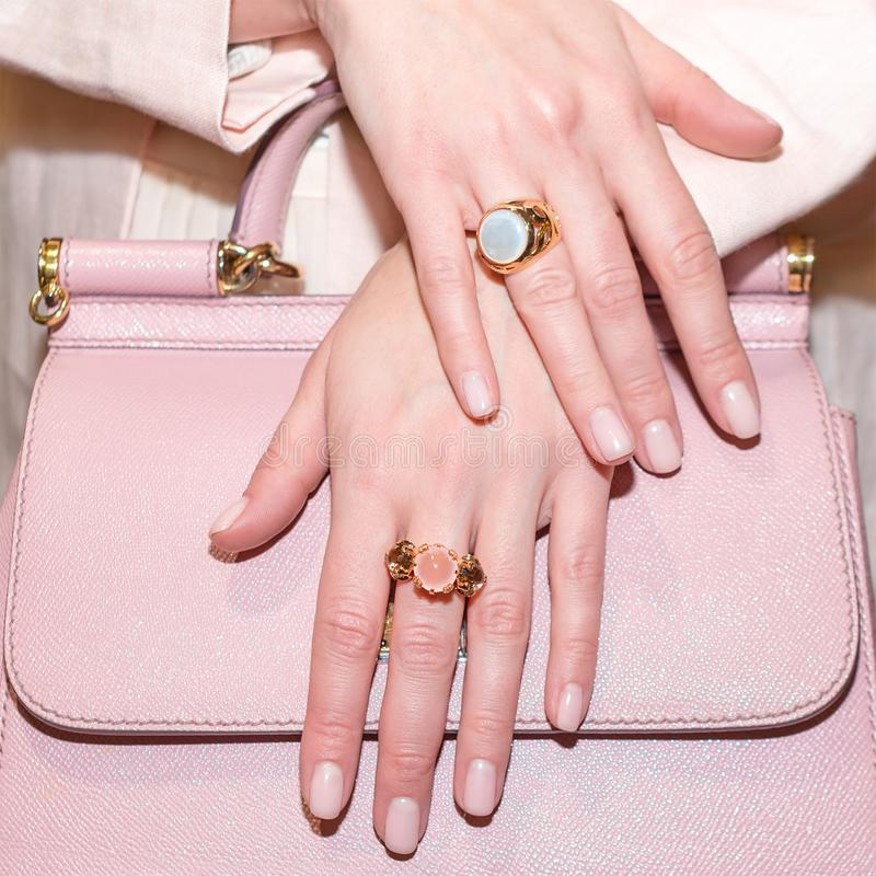 Woman hands with manicure and luxury jewelry rings. Close up of trendy leather pink bag with female hands showing. Fashion jewelry at camera. Concept of stock images