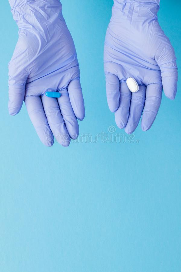 Woman hands in medical gloves giving two big pills. Blue and white. Make your selection royalty free stock images