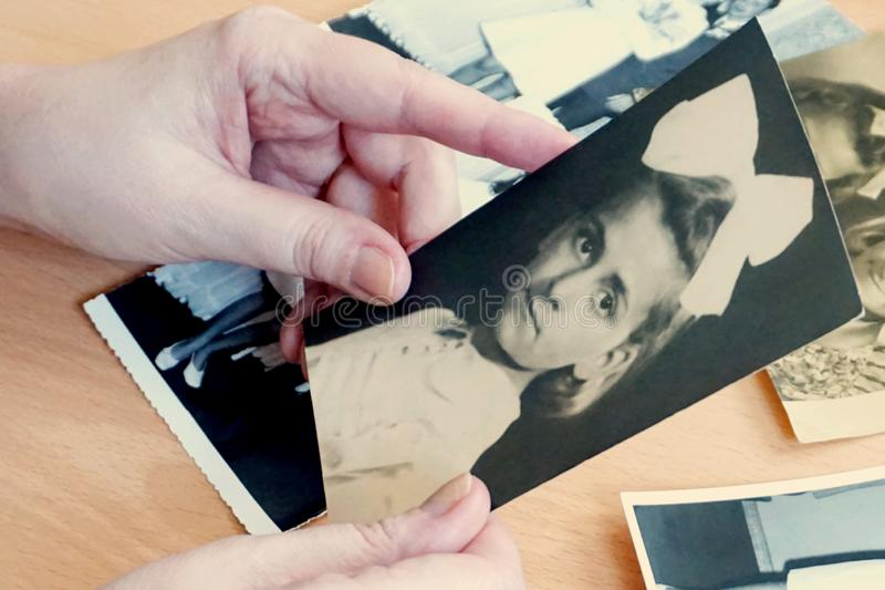 Woman hands with old vintage photo of girl. Woman hands with old vintage photo of young girl. Memories, sadness and sorrow concept, alone, loss, isolation, album stock photo