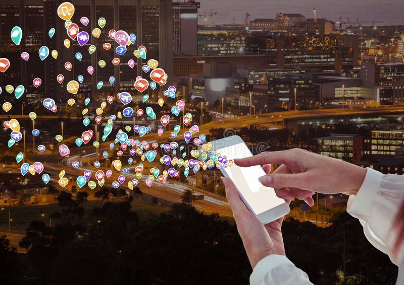 Woman hands with phone with application icons coming up form it. Blurred city at night. Digital composite of woman hands with phone with application icons coming royalty free stock photos