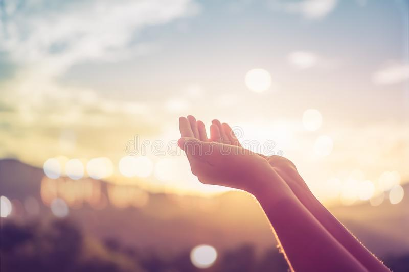 Woman hands place together like praying in front of nature green background. royalty free stock images