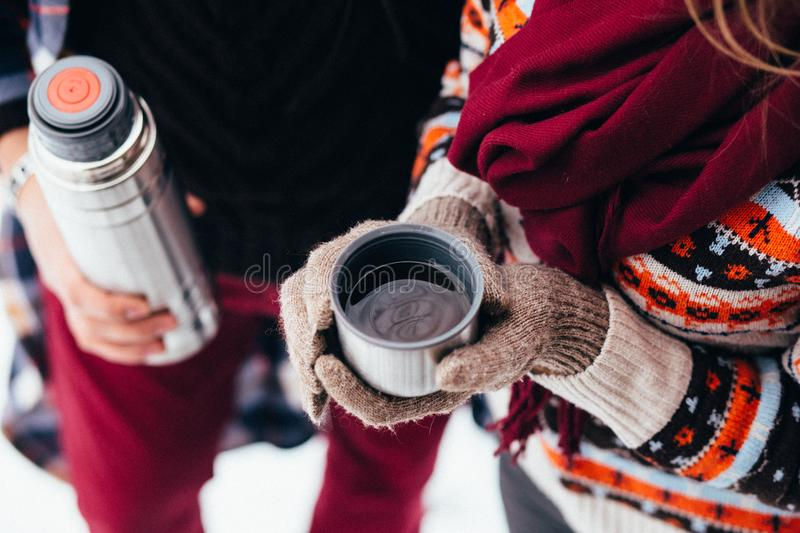 Woman hands pours hot tea or coffee out of thermos on winter forest background. girl using a thermos in on a snowy day. metallic c stock images