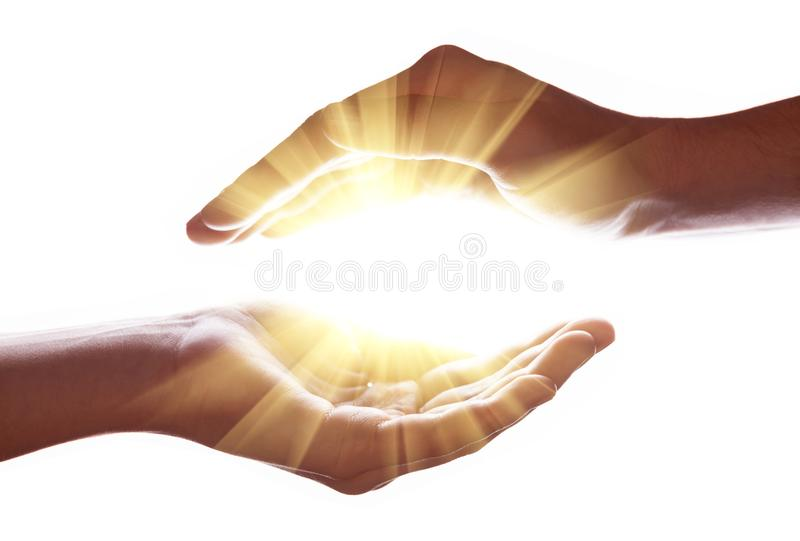 Woman hands protecting and containing bright, glowing, radiant, shining light. Emitting rays or beams expanding of center. Religion, divine, heavenly royalty free stock images