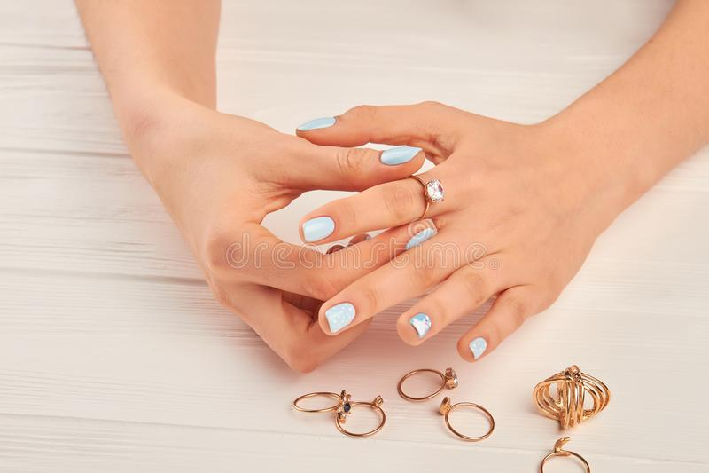 Woman hands putting on golden ring. Female manicured hands wearing golden ring with diamond. Woman well-groomed hands and jewelry stock photography