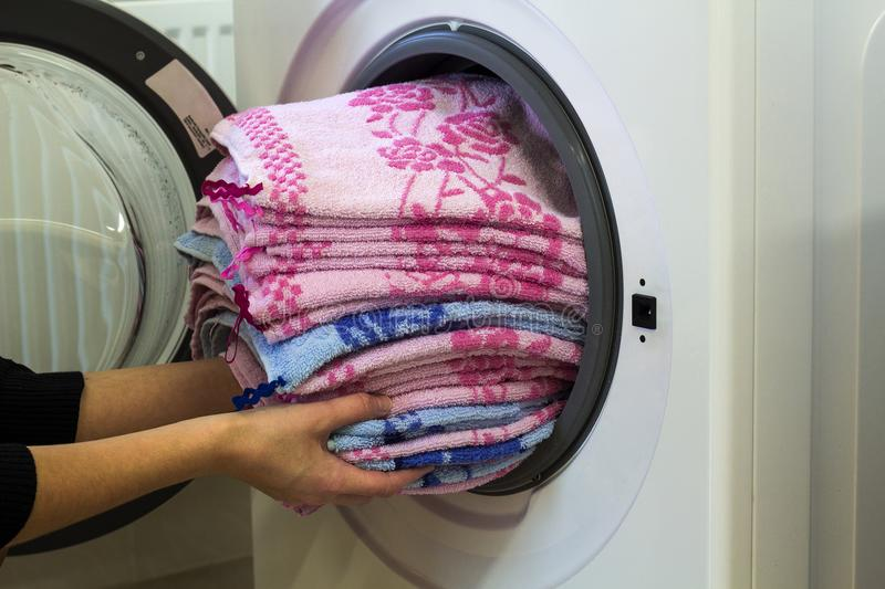 Woman hands putting laundry into washing machine at home.  stock image
