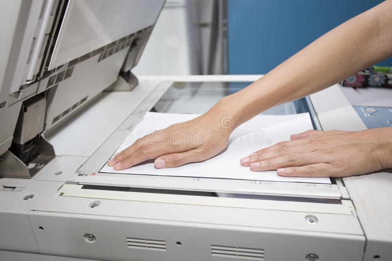 Woman hands putting a sheet of paper. Into a copying device stock photography