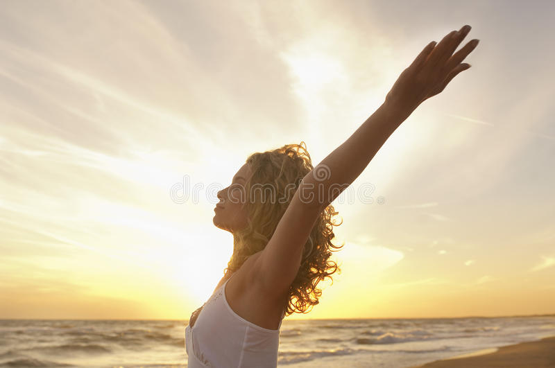 Woman With Hands Raised Meditating At Beach royalty free stock photo