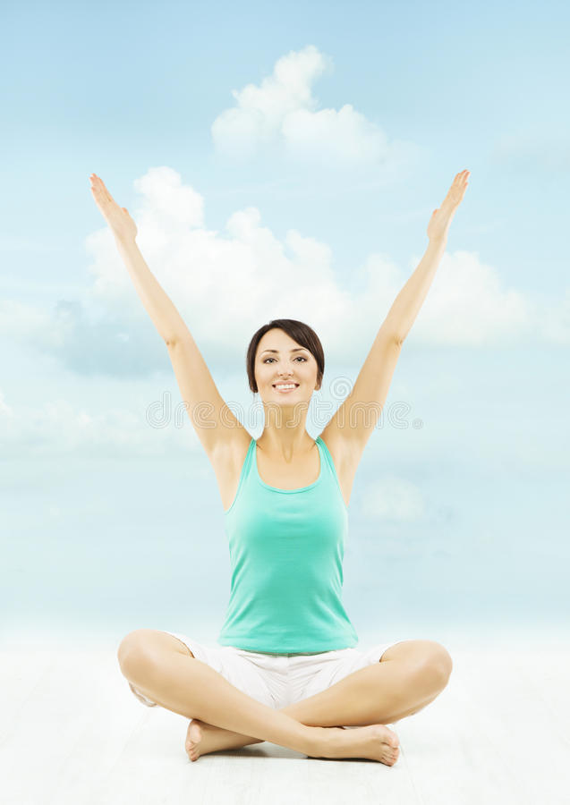 Woman hands raised up. Sitting in yoga lotus pose over sky background stock photography